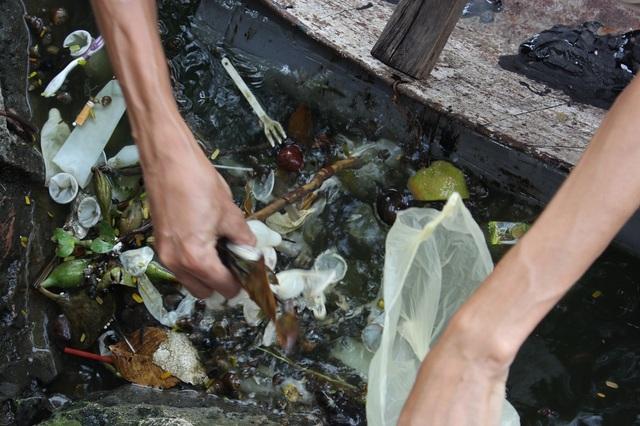 Một người đàn ông chèo thuyền ra vớt loại rác thải đặc biệt này.
