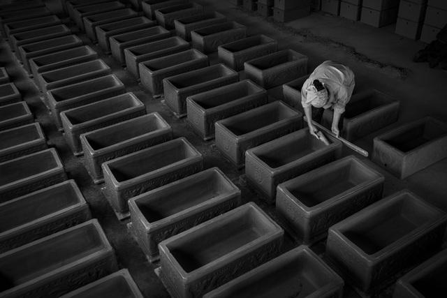 Ảnh đẹp trong ngày 11/5/2017. Một thợ thủ công hoàn thành quy trình cuối cùng trước khi đưa bình tiểu vuông vào lò nung. Theo truyền thống Việt Nam, khi người ta qua đời, cơ thể sẽ được chôn xuống mặt đất tự nhiên. Ba năm sau, sau một buổi lễ gọi là Cải Cát, cơ thể phân hủy hết chỉ những mẩu xương còn lại sẽ được chuyển đến các bình tiểu vuông để chôn cất vĩnh cửu. Trong các nghĩa trang lớn, có hàng ngàn những ngôi nhà như vậy nằm trong lòng đất.