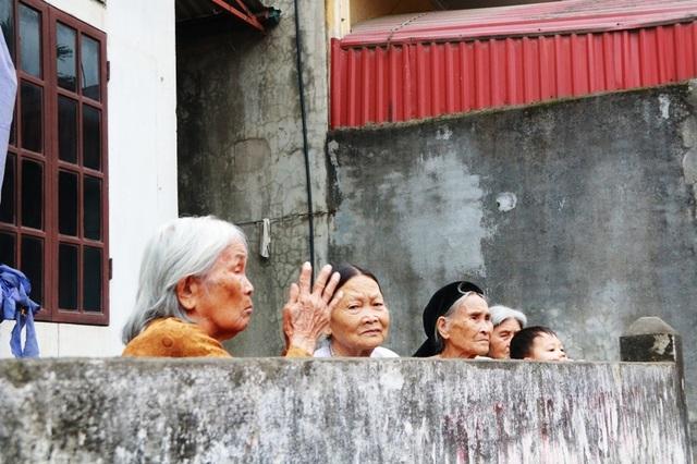 Những cụ bà cao tuổi không xuống gần kiệu để chui qua được nên đã khấn vái từ xa để cầu nguyện.