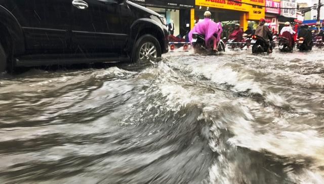 Nước mưa xối xả đổ từ dốc cao trên đường Võ Văn Ngân...