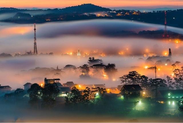 """Ngày 21/12 - ảnh của Thuần Võ: Bức ảnh """"City Lights"""" của Thuần Võ được chụp tại Đà Lạt, thức dậy vào một buổi sáng sớm và leo lên những ngọn đồi còn đang phủ sương, ánh đèn và những ngôi nhà mờ tỏ trong màn sương dày đặc đã tạo nên một cảnh quan kỳ diệu được thu lại trong ống kính Thuần Võ."""