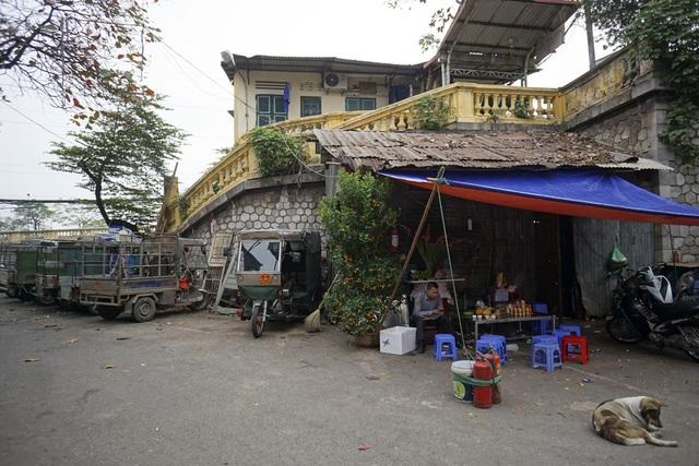 Dãy xe chở hàng xếp hàng dài bên một quán nước chè với lọ hoa, cây quất tại ga Long Biên.