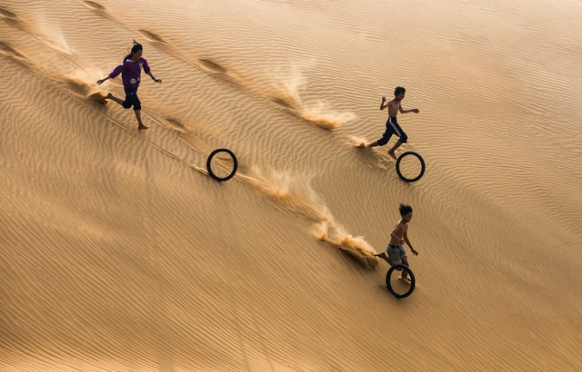 Ảnh đẹp nhất trong ngày 14/7/2017. Một nhóm trẻ em đùa vui khi chơi với lốp xe máy cũ trên cồn cát gần bãi biển Mũi Né, một thị trấn ven biển tỉnh Bình Thuận. Trò chơi đơn giản này được chơi bởi trẻ em khắp nơi trên thế giới.