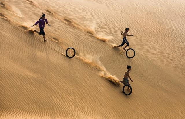 Một nhóm trẻ em đùa vui khi chơi với lốp xe máy cũ trên cồn cát gần bãi biển Mũi Né, một thị trấn ven biển tỉnh Bình Thuận. Trò chơi đơn giản này được chơi bởi trẻ em khắp nơi trên thế giới. Ảnh đẹp nhất trong ngày 14/7/2017 đăng trên tạp chí National Geographic của Trần Tuấn Việt.