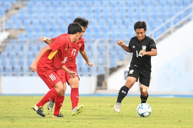 Các tuyển thủ U15 Việt Nam (áo đỏ, bên trái) ngăn chặn pha đi bóng của cầu thủ U15 Thái Lan (áo đen, bên phải)