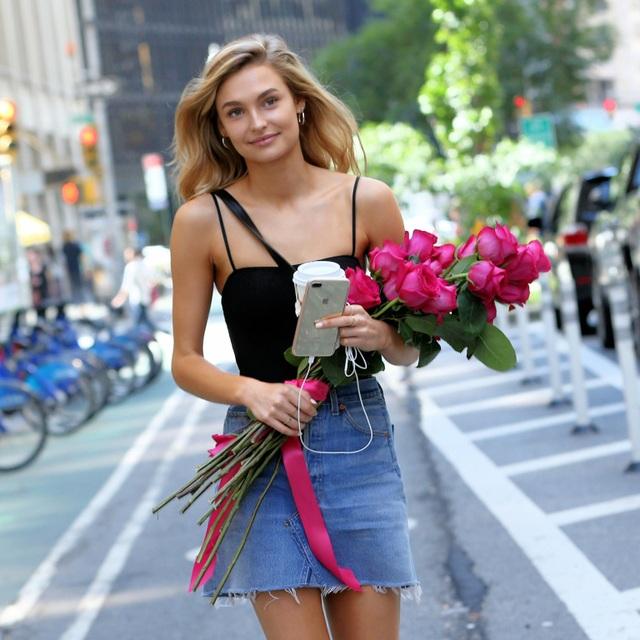 """Người mẫu Hà Lan Roosmarijn de Kok lựa chọn chiếc áo hai dây gợi cảm màu đen và một chiếc váy ngắn denim """"crop chân"""". Cùng với đôi khuyên tai hình vòng, de Kok lựa chọn cho mình một diện mạo đậm chất thập niên 1990."""