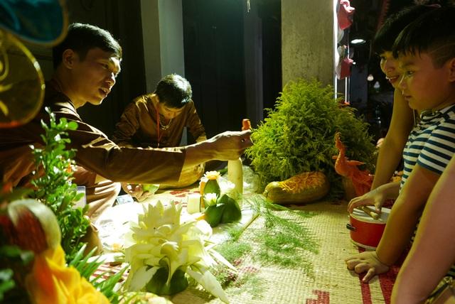 Nhiều gian tái hiện không khí Tết Trung thu cổ truyền. Trong ảnh, bé trai chăm chú xem các nghệ nhân cắt tỉa hoa văn, họa tiết trên hoa quả.