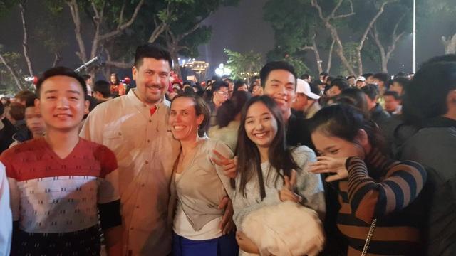 Nhóm bạn trẻ Việt Nam dạy cho một cặp đôi người nước ngoài cách phát âm câu Chúc mừng năm mới bằng tiếng Việt. (Ảnh: Thế Kha)