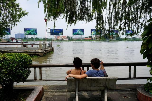 Hai bạn trẻ người nước ngoài ngồi nghỉ mát dưới hàng cây ven bến Bạch Đằng.
