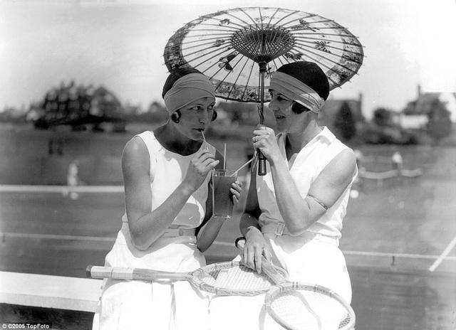 Hai người phụ nữ trong trang phục mang phong cách của thập niên 1920 nghỉ giải lao bên sân tennis.