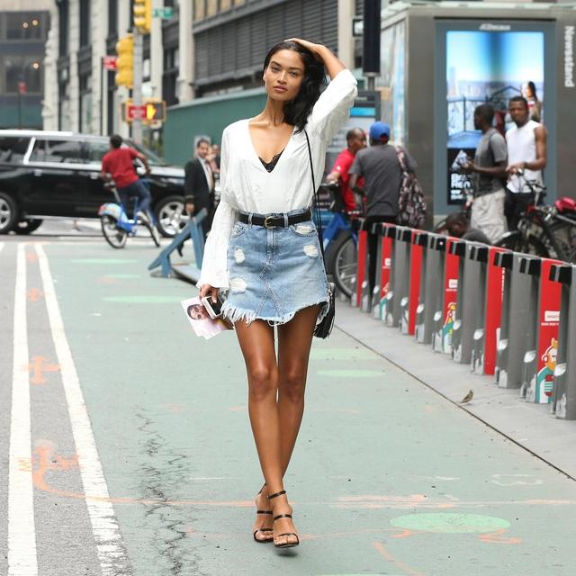 """Người mẫu Shanina Shaik cũng mặc váy ngắn denim """"xổ riềm chân"""", phá cách với áo trắng dài tay, bên trong lấp ló áo ngực đen. Các phụ kiện như dây lưng, túi xách, giày đều có tông màu đen."""