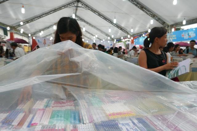 Du sách đã được phủ nilon tráng mưa, nữ độc giả vẫn cố gắng tìm sách.