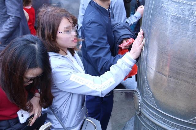 Nhiều bạn trẻ dùng tiền lẻ xoa lên mặt chuông ở chùa Đồng để lấy may, gây hình ảnh phản cảm.