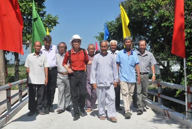 Tổng biên tập báo Dân trí Phạm Huy Hoàn cùng quý đại biểu và các cụ cao niên vui mừng đi qua cầu mới mang tên Dân trí