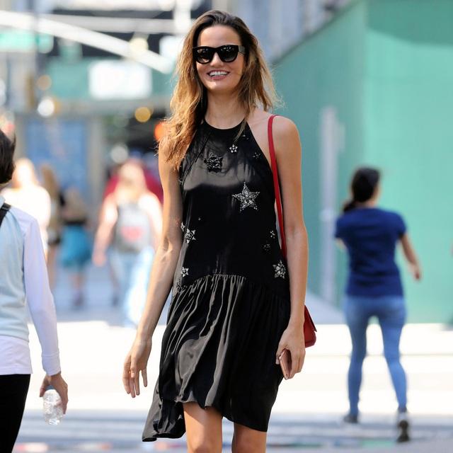 Người mẫu Barbara Fialho lựa chọn váy ngắn màu đen và một chiếc túi xách nhỏ màu đỏ.