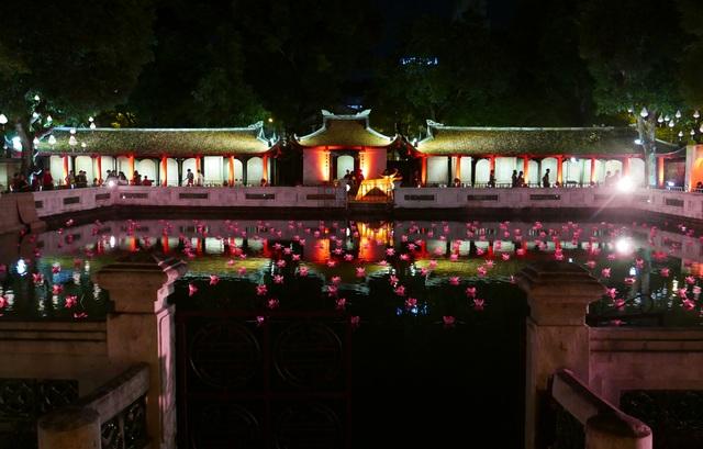 Khu bia tiến sĩ lung linh ánh đèn, trong khi mặt hồ được trang trí bởi hàng trăm hoa đăng hồng - đỏ.