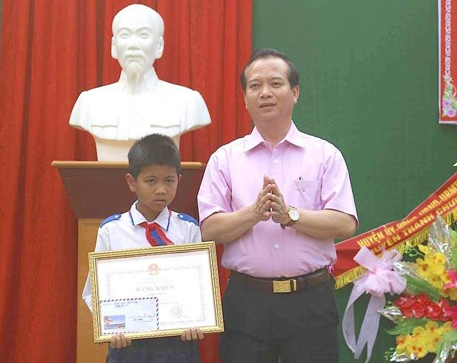 Ông Nguyễn Văn Quế - Chủ tịch UBND huyện Thanh Chương trao Bằng khen của Bộ GD&ĐT cho em Tú.