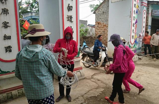 Người dân tháo dỡ các dây chăng chắn ở cổng làng.
