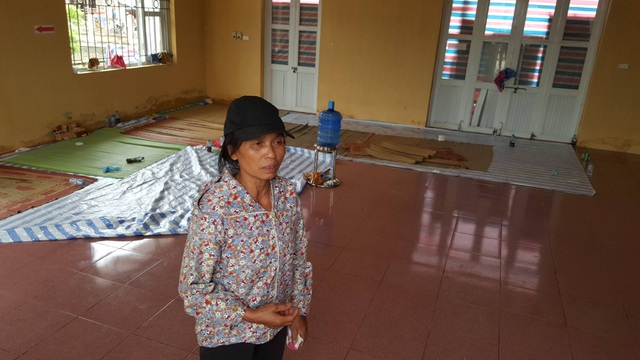 Một phụ nữ thôn Hoành đứng trong lòng nhà văn hóa thôn, nơi trước đó vừa giữ 19 CSCĐ. Ghi nhận tại đây khá sạch sẽ, hoàn toàn không có mùi xăng.