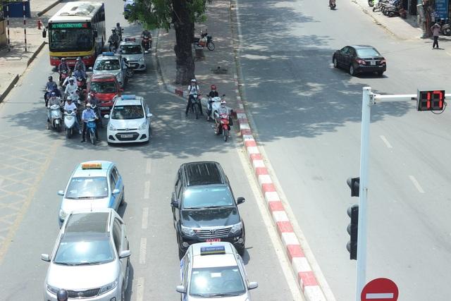 """Những người có việc phải lưu thông trên đường vào những ngày này tại Hà Nội đều có chung cảm giác khó chịu, ngộp thở và bóng rát như bị tạt lửa vào người. Trên nhiều tuyến đường, người dân tranh thủ đứng chờ đèn đỏ dưới những tán cây xanh để """"giảm nhiệt""""."""