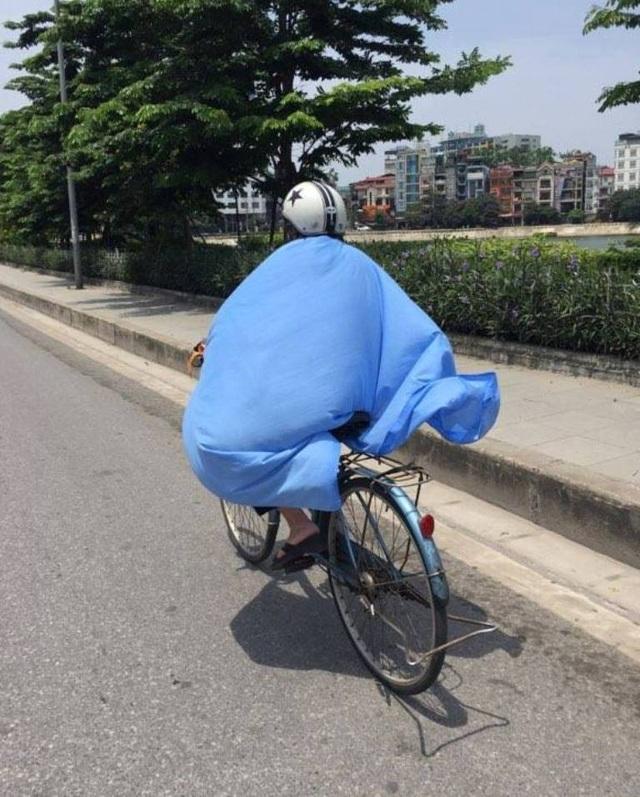 Một người phụ nữ phải chùm cả chiếc khăn choàng mỏng để che nắng. (Ảnh: Đ.N)