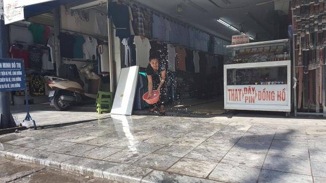 Trên phố Hàng Ngang, các chủ cửa hàng phải liên tục tạt nước để giảm nhiệt