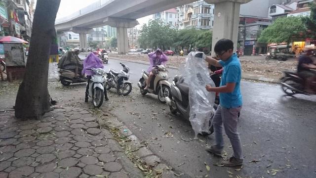 Người dân cuống cuồng mặc áo mưa khi giông thổi mạnh.