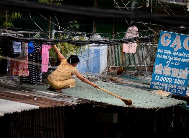 Người phụ nữ quét lớp đất bụi do hộ dân phía trên xả xuống.