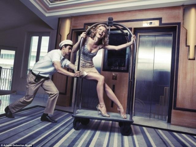 Người mẫu - nữ diễn viên người Séc - Eva Herzigová - thích thú khi được đẩy đi trong hành lang khách sạn bằng một chiếc xe đẩy hành lý.
