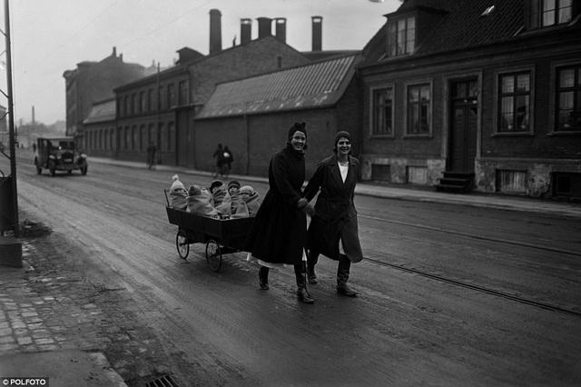 Hai người phụ nữ ở Copenhagen (Đan Mạch) mỉm cười khi kéo chiếc xe có một nhóm trẻ đang quấn chăn ngồi trên đó hồi năm 1930.