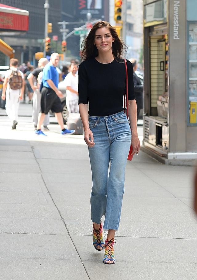 Người mẫu Hilary Rhoda mặc quần jeans cạp cao và một chiếc áo phông đen giản dị. Giày và túi xách có màu sắc tươi tắn, nổi bật.