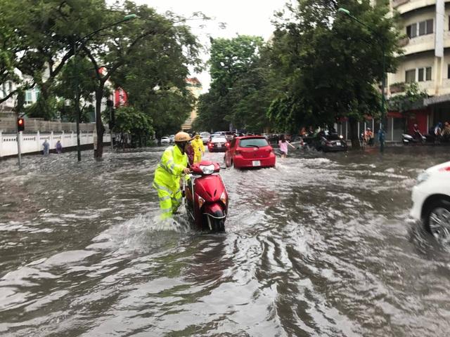 CSGT giúp dân dắt xe chết máy trên đoạn đường ngập sâu.