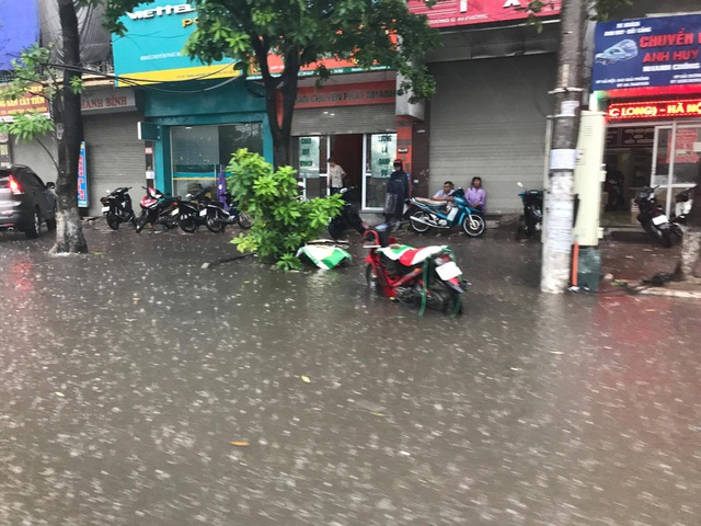 Mưa lớn, ngập trên đường giải phóng. Nhiều người đi xe máy phải bỏ xe lại trên đường, chạy vào hiên nhà dân trú mưa.