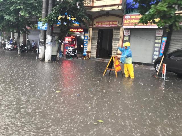 Nhân viên công ty thoát nước đội mưa canh cống trên đường phố Hà Nội.