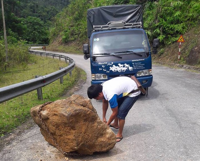 Anh muốn dùng dây xích kéo hòn đá vào lề đường.