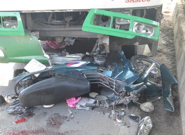 Chiếc xe máy bị tông hư hỏng nằm trước đầu xe buýt
