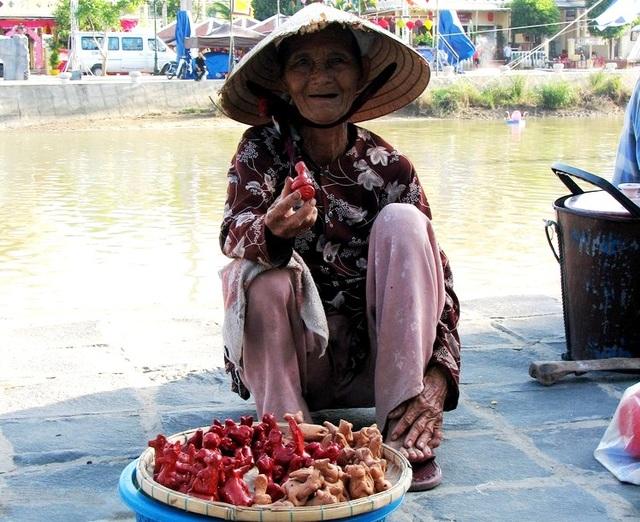 Một người bán con Tò-he bên bờ sông Hoài nở nụ cười thân thiện với du khách