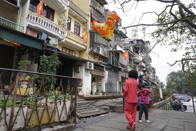 Những em nhỏ chơi bóng bay hình con gà bên đường tàu hỏa lâu đời chạy xuyên khu trung tâm tại phố Phùng Hưng.