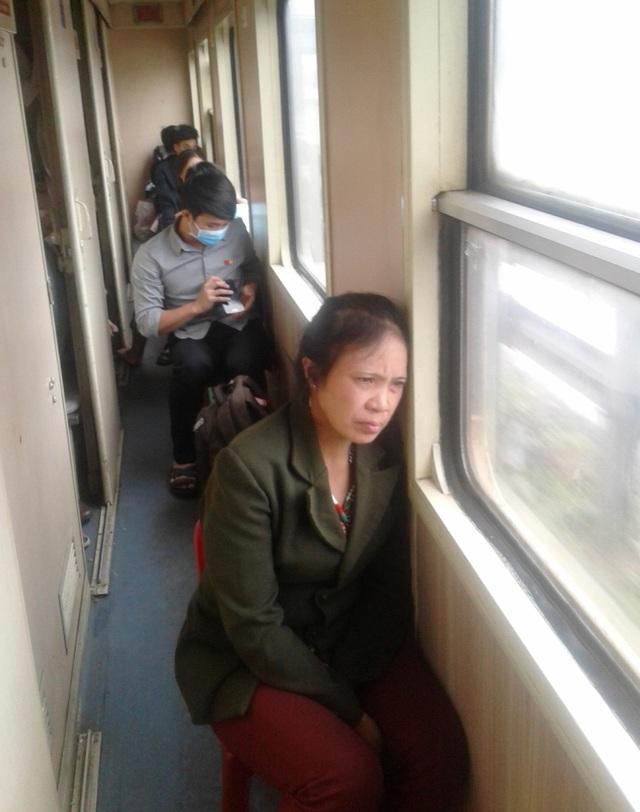 Hành khách mệt nhoài ngồi hành lang trên chuyến tàu Bắc - Nam