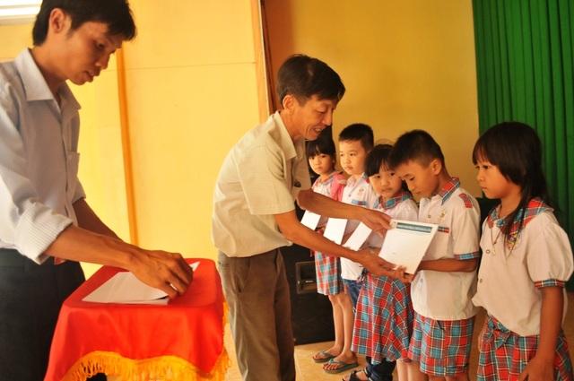 Ông Lê Thanh Tâm - Bí thư Đảng ủy xã Nhị Mỹ trao những suất học bổng của Công ty Grobest Việt Nam, Quỹ Khuyến học Việt Nam cho các em học sinh trường tiểu học Nhị Mỹ 1