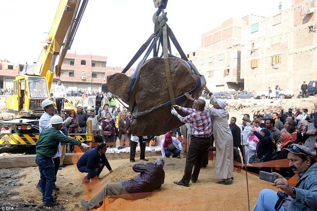 Các chuyên gia khảo cổ đã có mặt ở quận Souq al-Khamis thuộc thủ đô Cairo, Ai Cập, để chứng kiến khoảnh khắc cần cẩu đưa bức tượng ra khỏi bãi khai quật nằm trong một khu xóm nghèo.