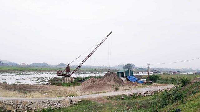 Một bãi tập kết cát trái phép tại xã Gia Trung, huyện Gia Viễn nằm ngay bên sông và đê tả sông Hoàng Long.