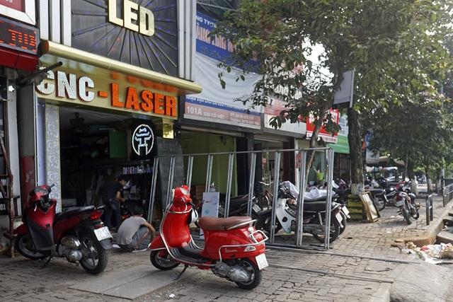 Trên đường Đại Cồ Việt, một cửa hàng làm biển hiệu đã coi vỉa hè như xưởng sản xuất của mình, chiếm gần hết lối đi dành cho người đi bộ.