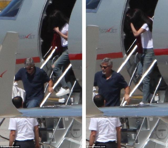George Clooney và vợ. George chịu trách nhiệm lần lượt xách từng chiếc nôi xuống máy bay.