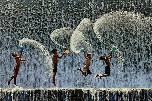 Những đứa trẻ nghịch nước dưới dòng thác lớn