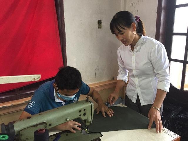 Chị Luyện đang hướng dẫn cho một công nhân tại xưởng may của mình