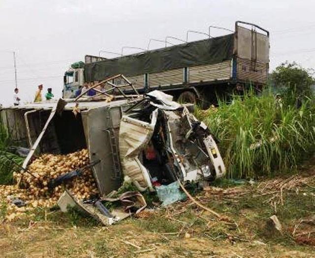 Sau cú tông mạnh, chiếc xe tải bị bẹp dúm cabin, nằm chỏng vó dưới ruộng.