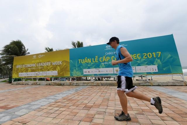 Khách du lịch chạy tập thể dục qua một tấm pa nô lớn trên đường dọc bờ biển.