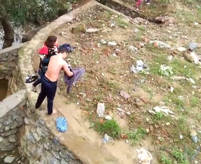 Anh Cường được người dân đưa áo quần cho mặc sau khi cứu người nhảy sông (Ảnh do người dân cung cấp).