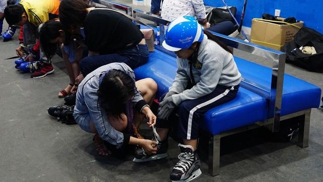 Người mẹ này đang chỉnh lại dây giày cho con